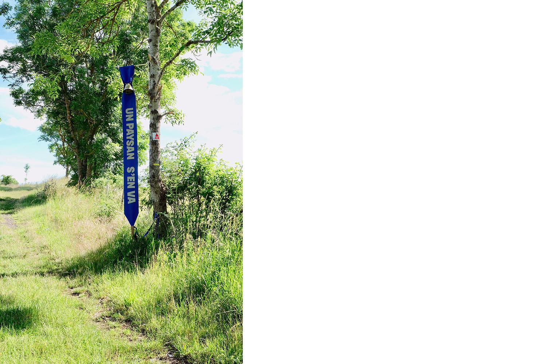 """banderole """"un paysans s'en va"""" installée au départ d'une randonnée"""